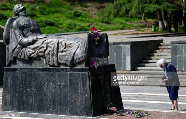 An elderly woman holding candles stands by the Unknown Soldier Tomb memorial during the Victory Day celebrations in Tbilisi on May 9, 2021. - Georgia...