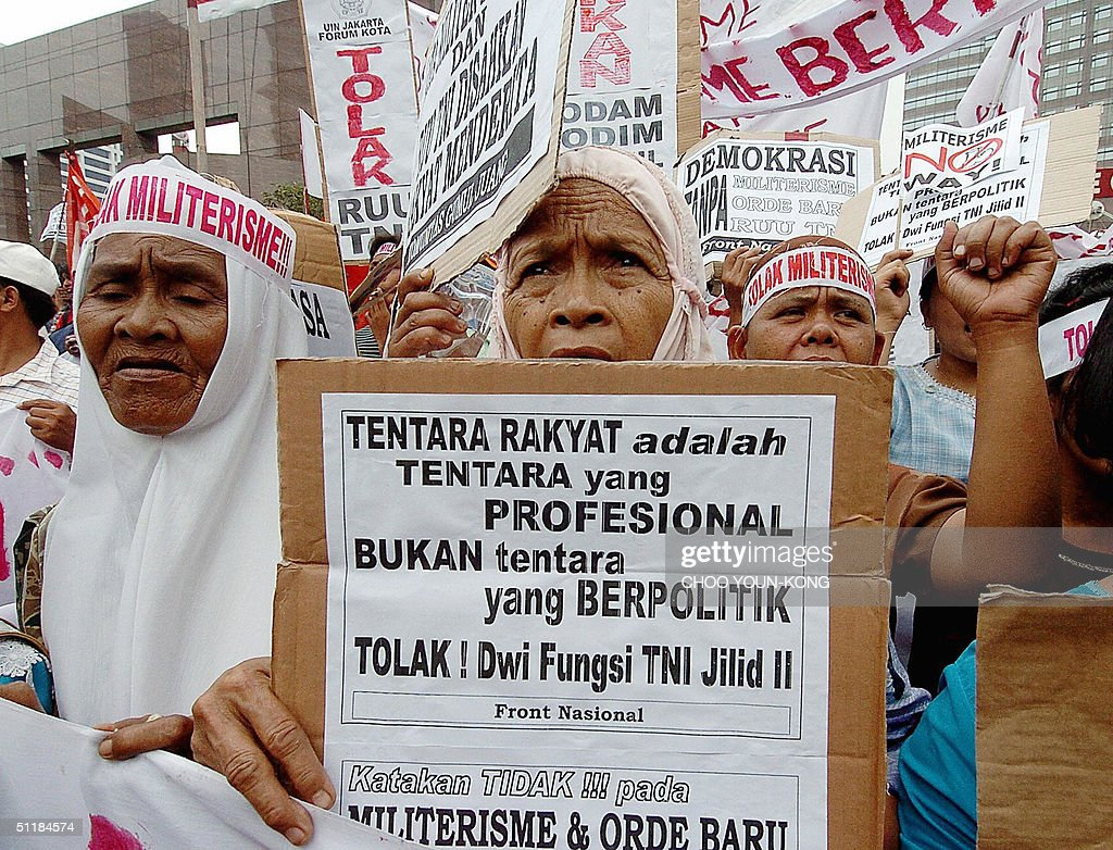 An elderly woman holds a placard that re : News Photo