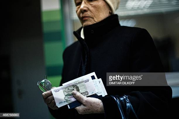 An elderly woman holds her pension received in Russian ruble notes in the eastern Ukrainian city of Donetsk on April 1 2015 The yearlong conflict in...