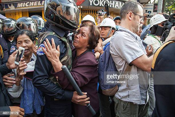 An elderly woman hugs a member of the municipal security forces after having been pushed away during a demonstration to retake the opposition's base...