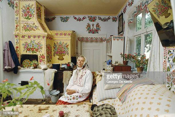 An elderly woman in a home decorated with floral stencils circa 1989