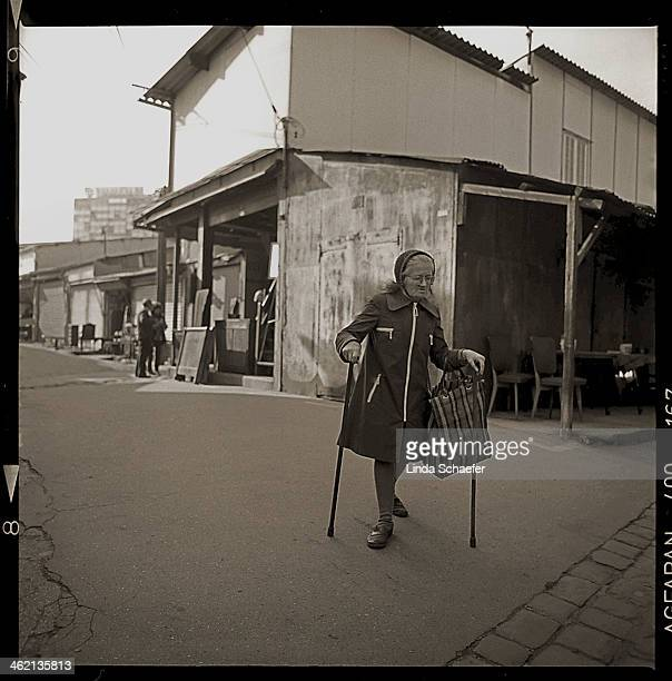 An elderly woman in a raincoat walks with the help of two canes in Paris. The photograph was taken with a Rolleiflex camera