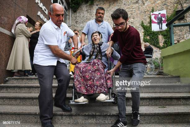 An elderly woman in a wheelchair is helped down some stairs as she leaves Haci Sabanci polling station where he will cast his vote in the Turkish...