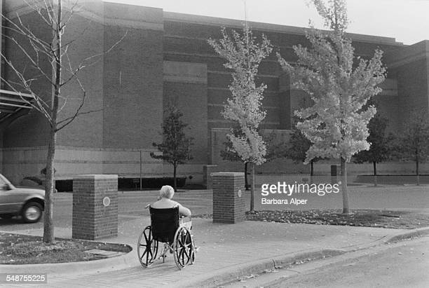 An elderly woman in a wheelchair outside the Somerset Collection a mall in Troy Michigan USA September 2001