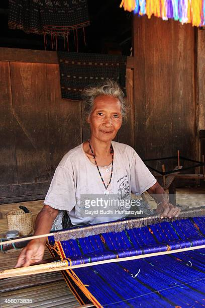 An elderly woman in Bena village posing while weaving Ikat. Weaving activities is the famous traditional home industry to produce woven fabrics...