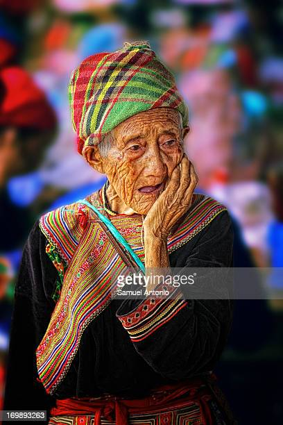 CONTENT] An elderly woman in traditional clothing from the Flower Hmong hill tribe in a candid moment at the colorful ethnic minority Bac Ha Sunday...