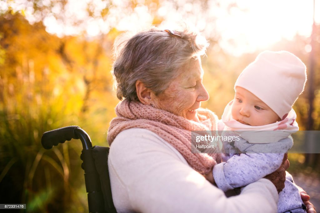 An elderly woman in wheelchair with baby in autumn nature. : Stock Photo