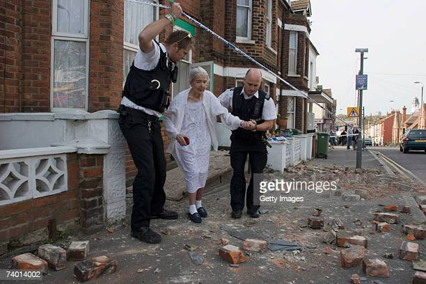 An elderly woman is escorted from her home through fallen smoke stacks and chimney rubble, after an earthquake April 28, 2007 in Folkestone, United...