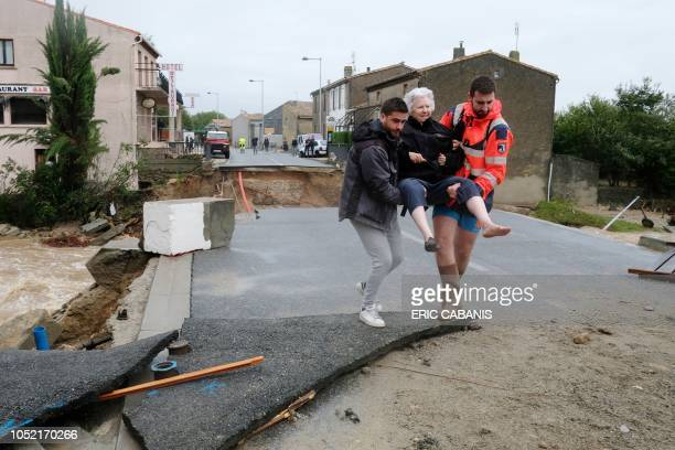 TOPSHOT An elderly woman is evacuated on October 15 2018 in Villegailhenc in the Aude department after it was particularly badly hit by heavy rain...