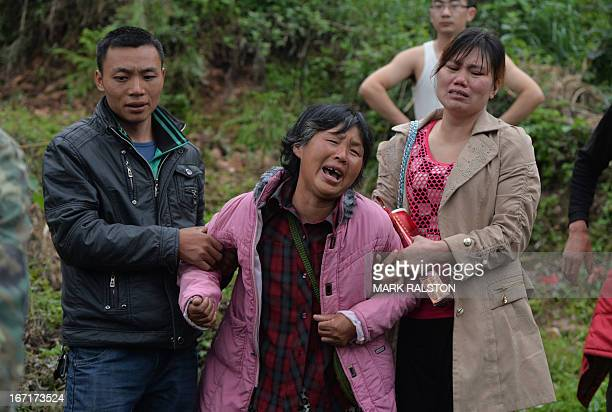 An elderly woman is helped by her children as she mourns at the funeral of her husband after a magnitude 70 earthquake hit Lushan Sichuan Province on...