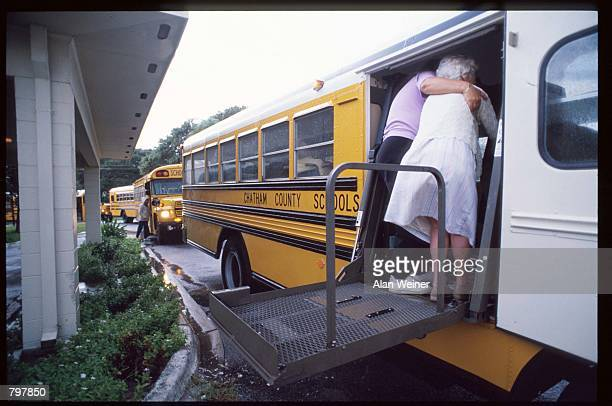 An elderly woman is helped onto a school bus September 22 1989 in Charleston SC Hurricane Hugo blasted the South Carolina coast with sustained winds...