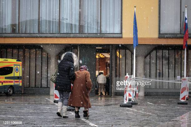 An elderly woman is helped to walk towards the vaccination centre on February 11, 2021 in Kranj, Slovenia. Slovenia plans to vaccinate 5% of its 2...