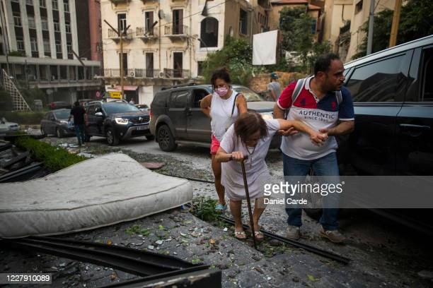 An elderly woman is helped while walking through debris after a large explosion on August 4, 2020 in Beirut, Lebanon. Video shared on social media...
