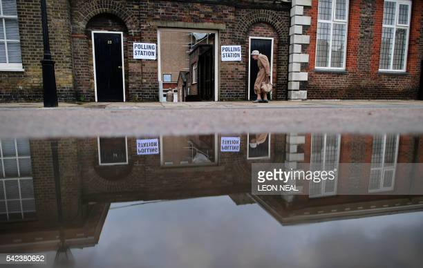 An elderly woman is reflected in a puddle of rain water as she arrives at a polling station at the Royal Hospital in Chelsea west London on June 23...