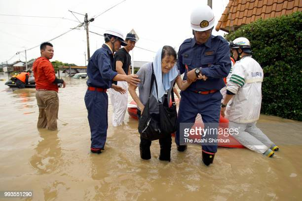 An elderly woman is rescued as the Mabicho area is submerged after Odagawa River banks collapse due to heavy rain on July 7 2018 in Kurashiki Okayama...