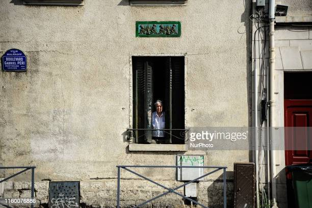 An elderly woman is seen looking from a window at Malakoff district in Paris France on August 06 2019