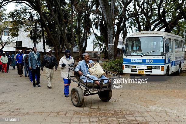 An elderly woman is transported to a voting station in a cart on July 31 in Harare Zimbabwe Thousands of people came out today to take part in the...