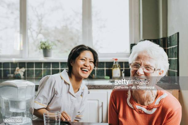 an elderly woman laughs beside a friendly young care assistant - communication stock pictures, royalty-free photos & images
