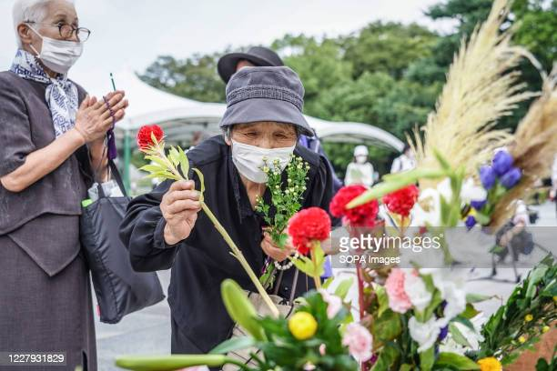 An elderly woman lays flowers at the Hiroshima Peace Memorial Ceremony Hiroshima marks the 75th anniversary of the US atomic bombing which killed...