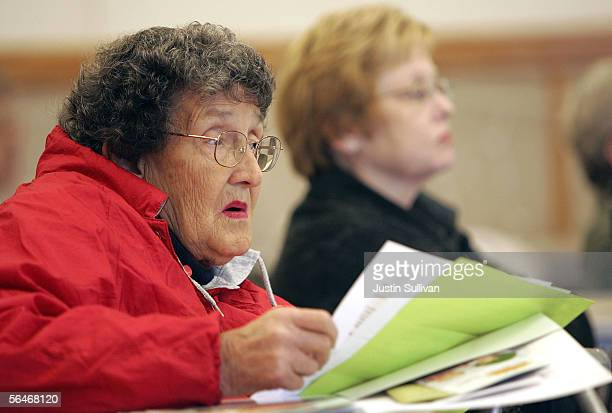An elderly woman listens to a seminar on how to sign up for the new Medicare drug prescription program during a Medicare enrollment event December 19...