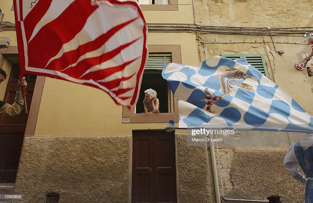 An elderly woman looks at two Standard bearers belonging to the Onda (Wave) and the Giraffe on June 28, 2004 in Siena, Italy. The city?s 17 separate Contrade or neighbourhoods vie to compete in the prestigious race, which takes place at the end of a week of festivities which encourage huge support and fierce competion between the participants.