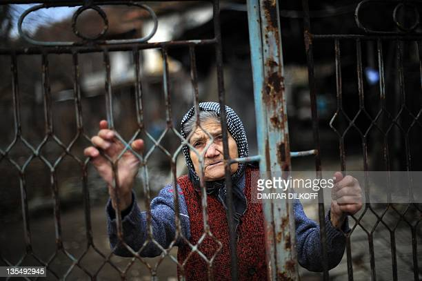 An elderly woman looks on December 6 2011 through the gate of her house in the village of Chichil some 100 kms north of the capital Sofia at the...