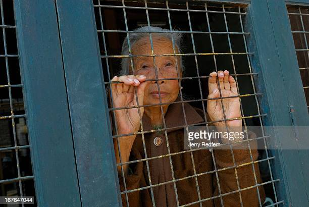 An elderly woman looks out at the street from behind the grille of her front door in Kengtung
