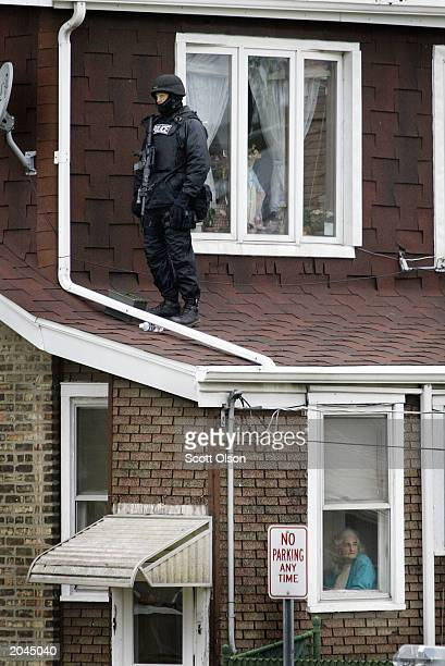 An elderly woman looks out the window of her home as a police marksman watches the activity at a Ku Klux Klan rally in the park across the street May...
