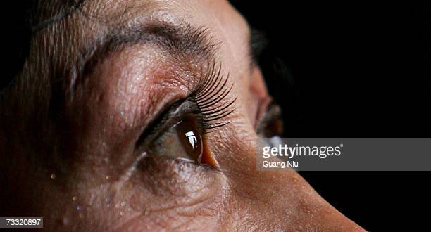 An elderly woman looks through a window after she put on her makeup and a pair of fake eyelashes before taking part in a traditional dance...