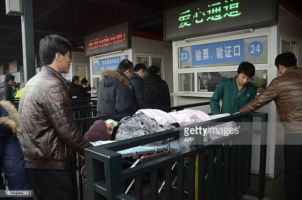 An elderly woman lying on a stretcher prepares to take a train at the entrance of the Beijing railway station on January 28 2013 The world's largest...