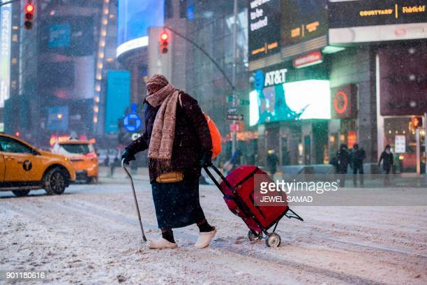 An elderly woman makes her way during a winter storm in New York on January 4 2018 The US National Weather Service warned that a major winter storm...