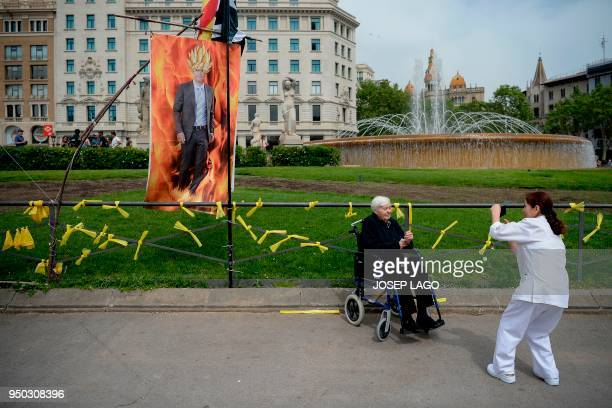 An elderly woman on a wheelchair poses for a picture in front of a banner depecting Catalonia's ousted leader Carles Puigdemont characterized as Goku...
