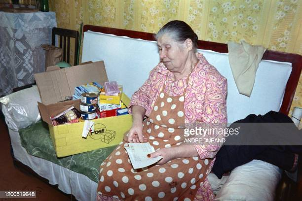 An elderly woman opens a food parcel, on December 9, 1990 in Moscow from the International aid to prodide the Muscovites facing difficulties in...