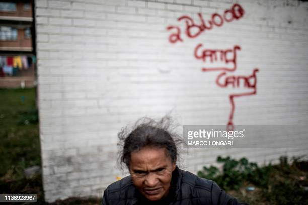 An elderly woman passes by a graffiti written on a wall in Johannesburg on April 23 2019 during a protest against the lack of service delivery or...