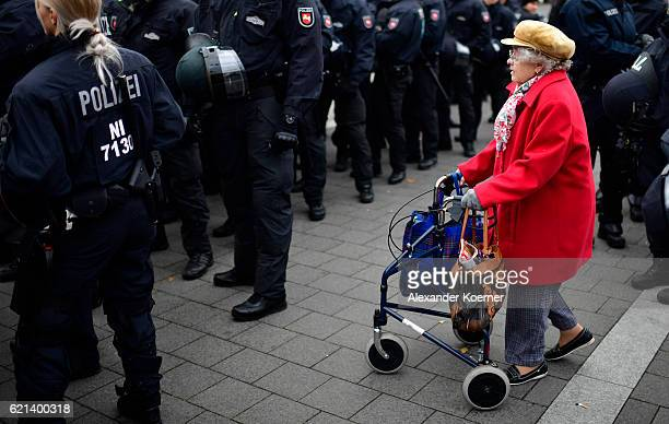 An elderly woman passes by anti riot police forces at the main train station ahead of the arrival of fans of Hannover 96 for the Second Bundesliga...