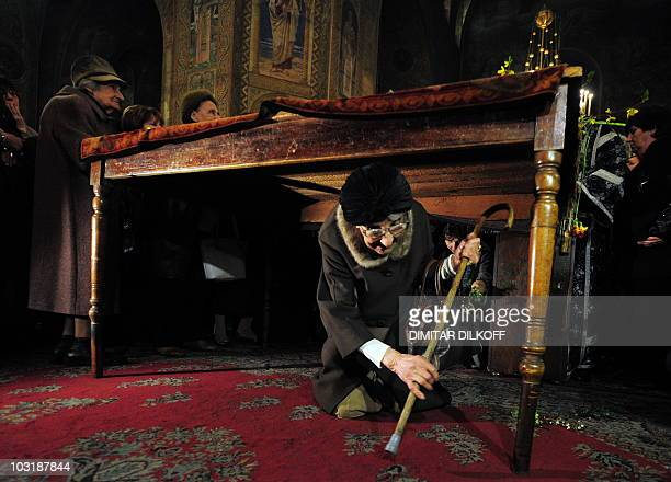 An elderly woman passes under a table where the Bible is placed during the Good Friday service in the goldendomed Alexander Nevski cathedral in Sofia...