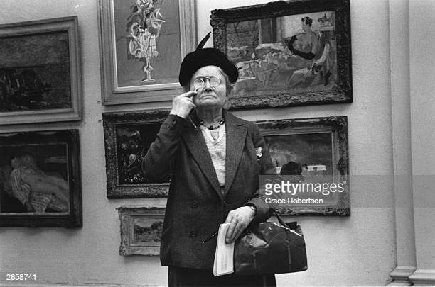 An elderly woman peers at a painting through a magnifying glass at the Tate Gallery London Original Publication Picture Post 9112 Tate Gallery unpub