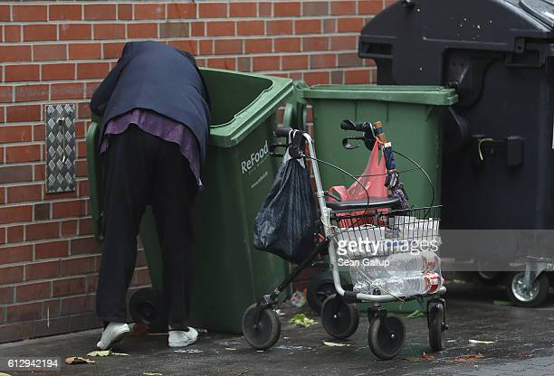 An elderly woman picks out discarded grocery items from a recycling bin behind a supermarket on October 6 2016 in Berlin Germany The number of...