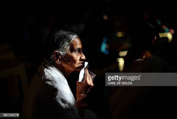 An elderly woman prays at the Oshwal centre at the beginning of a 24 hour Jain prayer vigil for victims of the Westgate mall massacre on September 28...