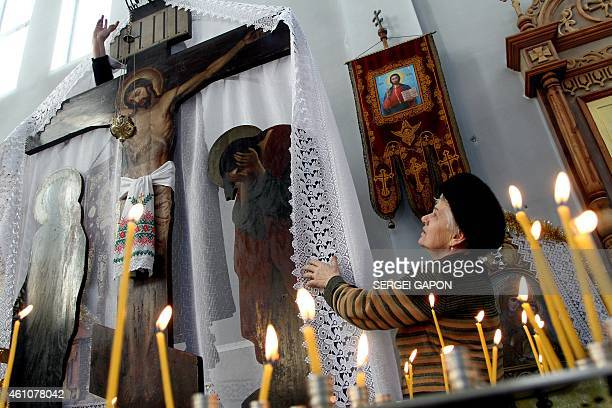 An elderly woman prepares a church on the day marking the Orthodox Christmas eve in the Belarus town of Smorgon some 125 km northwest of Minsk on...
