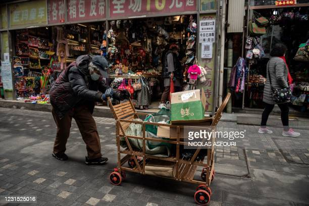 An elderly woman pushes a cart after searching through rubbish bins to collect recyclable items to sell, along a street near the Great Hall of the...
