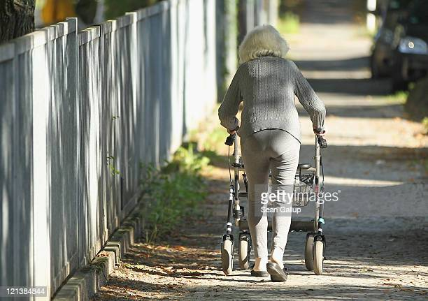 An elderly woman pushes a walker along a sidewalk on August 18 2011 in Berlin Germany Demographers are predicting that the elderly portion of...