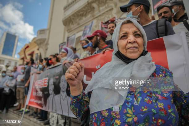 An elderly woman raises fist as others raise posters of Yassine Ayari, during a demonstration held in Tunis, Tunisia, on September 11 to call for the...