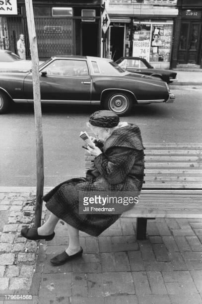 An elderly woman reads a book on a bench New York City 1977