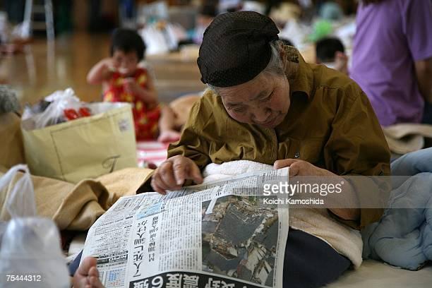 An elderly woman reads a newspaper amongst residents gathered inside the gymnasium of Kashiwazaki elementary school on July 17 2007 in Kashiwazaki...