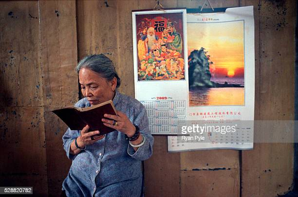 An elderly woman reads from her prayer book in the Hall of Great Benevolence at the Nanputuo Temple in Xiamen. The Nanputuo Temple is located on the...