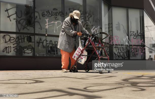 An elderly woman reads messages spray painted on the ground at 3rd Street and Fairfax in the Fairfax District on Sunday May 31 2020