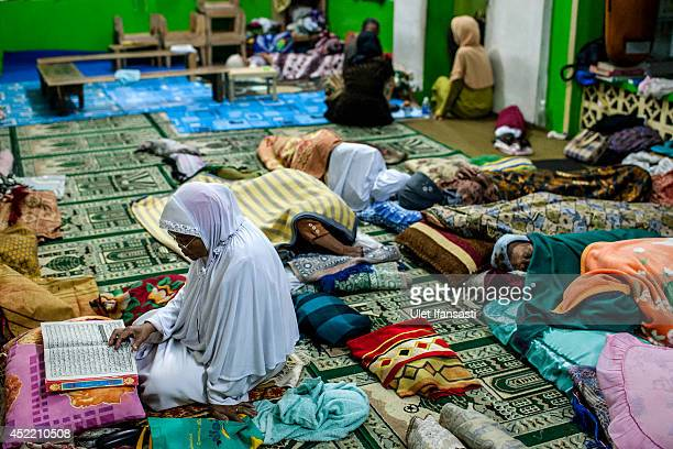 An elderly woman reads the Quran at a boarding school Sepuh Payaman that cares for the elderly during Ramadan on July 15 2014 in Magelang Central...