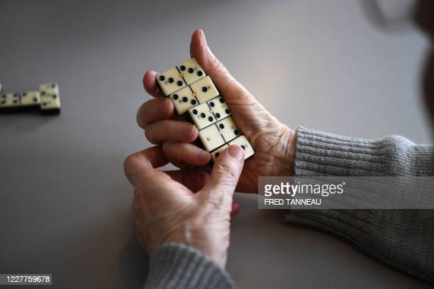 An elderly woman, resident of an EHPAD in Ploudalmezeau, western France, plays dominoes, on July 23, 2020. - The EHPAD in Ploudalmezeau banned visits...
