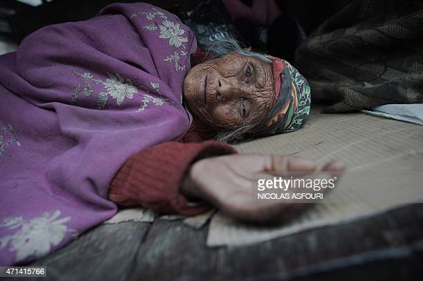 An elderly woman rests in a makeshift tent following an earthquake in the Nepalese capital Kathmandu on April 28 2015 Hungry and desperate villagers...